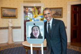 Photo of President Obama standing next to an electronic device with a viewscreen featuring the face of a smiling Asian American woman
