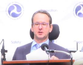 Image of Henry Claypool sitting in his wheelchair behind a podium and in front of a backdrop with US Department of Transportation logos